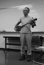 三線(さんしん)で沖縄の唄を披露する鈴木正輝さん